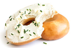 Plain bagel spread with cream cheese and chives, bite missing. I Stock Photo