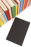 Plain black book front cover with row of colorful books isolated on white background. Plain black book with row of colorful booksisolated on a white background Stock Image