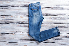 Plain blue jeans. Casual jeans on wooden background. Regular fit pants on showcase. Brand new denim garment Royalty Free Stock Images