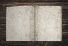Plain book. Open plain page vintage book with stained yellowed paper on dark brown wooden surface Stock Images