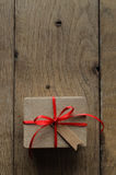Plain Brown Gift Box with Red Ribbon and Vintage Style Blank Tag Royalty Free Stock Image