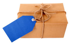 Plain brown paper package or parcel, blue gift tag or label, isolated on white Royalty Free Stock Photography