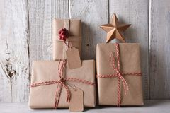 Plain brown paper wrapped Christmas presents. The presents are leanng on a rustic whitewashed wall royalty free stock photo