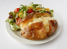 Plain Butter Jacket Potato with side salad. A plain butter baked potato on a plate with side salad Royalty Free Stock Images
