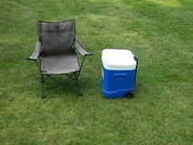 Plain Camping Chair And Blue Cooler On Open Lawn Stock Photo