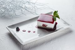Plain cheesecake coated with fruit jam on a square plate royalty free stock photography