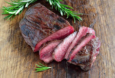 Plain cut beefsteak. Plain cut juicy beefsteak on a wooden board stock images