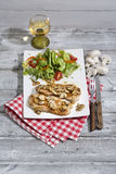 Plain cutlet served with mixed salad and white wine Stock Image