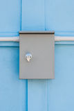 Plain Electric Control Enclosure on Blue Concrete Wall.  Royalty Free Stock Photo