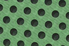 Plain green wooden surface with cylindrical holes Royalty Free Stock Photography