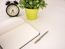 Plain notebook with a pen and clock. On white table Stock Image