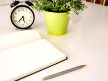 Plain notebook with a pen and clock. On white table Royalty Free Stock Photography
