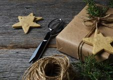 Plain Paper Wrapped Christmas Present Star Cookies Twine and Greenery. Christmas present wrapped in plain brown paper on a rustic wood table with holiday cookies stock images