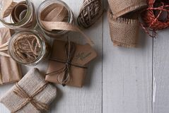 Plain paper wrapped Christmas presents. Top view of a group of plain paper wrapped Christmas presents with canning jars filled with string, twine and ribbon stock photo