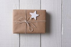 A plain paper wrapped Christmas presents with a wood star blank gift ta. Top view of a plain paper wrapped Christmas presents with a wood star blank gift tag stock photography
