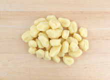 Plain potato gnocchi on a wood counter top. Top view of a portion of plain potato gnocchi on a wood counter top Royalty Free Stock Photo