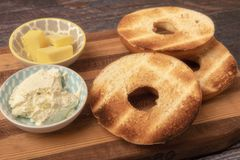 Plain toasted bagel with butter and cheese. On wooden background royalty free stock photos