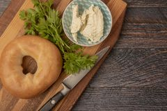 Plain toasted bagel with cheese and herbs on wooden chopping board. With copy space stock images