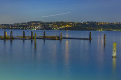 Plain trails at night with the dock and old wooden pillars. The bay in Tacoma Washington at sunset and into nightfall royalty free stock images