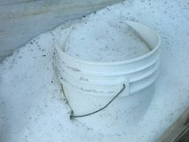 Plain White Bucket In Snow. Plain white bucket laying outside during wintertime in a wooden crate Royalty Free Stock Photography