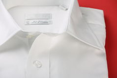 Plain white business shirt. Close up of plain white business or formal shirt with open neck on a red textured paper background royalty free stock images
