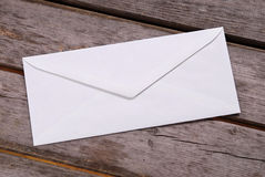 Plain white envelope. On a wood picnic table stock images