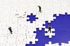 Plain white jigsaw puzzle and Businessman. Royalty Free Stock Photo