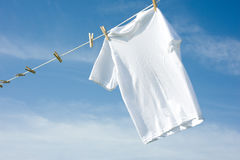 Plain White T-Shirt on a Clothesline. A plain white T-shirt hanging on a clothesline on a beautiful, sunny day, add text or graphic to shirts or copy space stock photos
