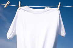 Plain White T-Shirt on a Clothesline. A plain white T-shirt hanging on a clothesline on a beautiful, sunny day, add text or graphic to shirts or copy space stock images