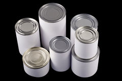Plain white tin cans. Seven tin cans of different sizes with white labels on black background Royalty Free Stock Photos