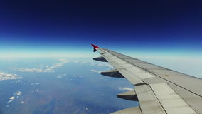 Plain wing from the window. Airplane wing and landscape seen from the plane window stock footage