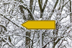 Plain yellow arrow sign in the snow pointing left Royalty Free Stock Image