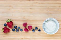 Plain yoghurt in bowl with fresh berries on wooden board. Closeup of plain yoghurt in bowl with fresh berries on wooden board stock photos