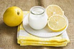 Plain yogurt in a jar with lemon. A setting of plain yogurt, lemons and checkered napkins on canvas Stock Image