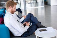 Plaine d'attente de voyageur d'affaires à l'aéroport Photographie stock libre de droits