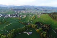 Plaine suisse avec des villages, des fermes et les Alpes à l'arrière-plan image stock