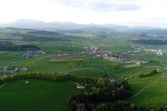 Plaine suisse avec des villages, des fermes et les Alpes à l'arrière-plan photos stock