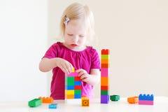 plaing与五颜六色的块的逗人喜爱的小孩女孩 库存照片