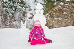 plaing与在多雪的冬天步行的一个雪人的愉快的漂亮的孩子女孩 图库摄影
