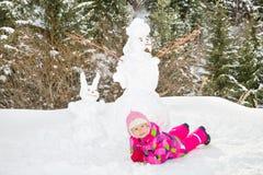 plaing与在多雪的冬天步行的一个雪人的愉快的漂亮的孩子女孩 免版税库存照片