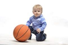 plaing与篮球球的小男孩在工作室 库存照片