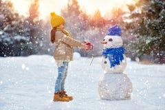 plaing与雪人的儿童女孩 免版税库存图片