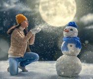 plaing与雪人的妇女 免版税库存照片