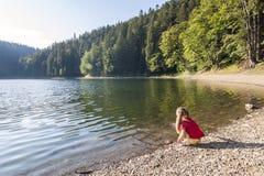 plaing在一个山湖的银行的一个逗人喜爱的小女孩wa的 图库摄影