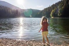 plaing在一个山湖的银行的一个逗人喜爱的小女孩wa的 免版税库存图片