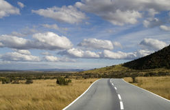 The plains highway. Highway running trough the plains under a blue white cloud sky stock photo