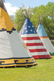 Plains Indian Teepees. Three tepees stand out against green grass and blue sky royalty free stock photography