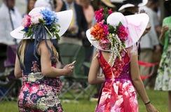 Women wearing flower hats at The Virginia Gold Cup. The Plains, Virginia/USA-5-19-17: Women walk through the crowd at The Virginia Gold Cup Royalty Free Stock Image
