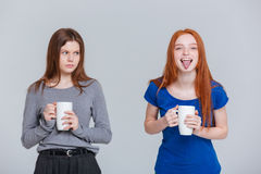 Plaisanterie deux heureuse et jeunes femmes de froncement de sourcils tristes buvant du thé photo stock