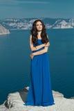 plaisir Façonnez la belle femme heureuse dans la longue robe au-dessus du bleu Images stock